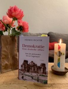 Das Buch mit Pfingstrosen und Osterkerze.